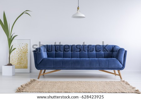 Blue sofa and wicker carpet in white simple living room - Shutterstock ID 628423925