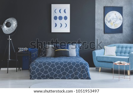 Blue sofa in bedroom interior with navy blue bed against dark wall with gallery of posters #1051953497