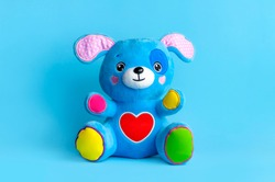 Blue soft children's toy puppy with funny ears, multi-colored paws and red heart on blue background flat lay copy space. Plush toy dog, baby friend, children's play item, happy childhood