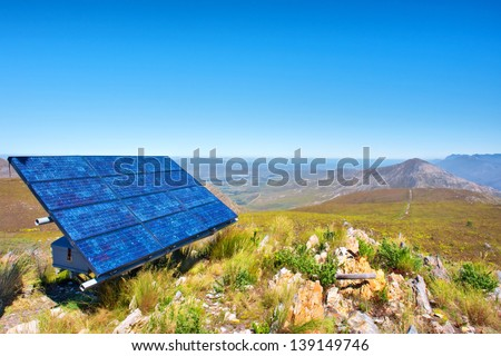 Blue solar cells against awesome mountain landscape. Shot in Salmonsdam Nature Reserve, near Hermanus and Stanford, Western Cape, South Africa.