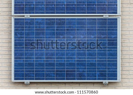 Blue solar panels attached to a vertical wall of a house