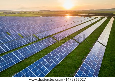 Blue solar photo voltaic panels system producing renewable clean energy on rural landscape and setting sun background.