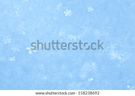Blue sparkling snow background with white little snowflakes.