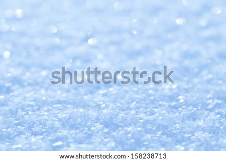 Blue sparkling snow background with white little snowflakes