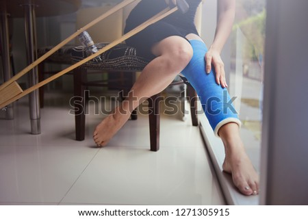 Blue splint knee. Bandaged leg cast and toes after a running injury accident.Young woman in blue plaster cast. Cropped shot of a girl holding her leg in pain. Shin splints. #1271305915