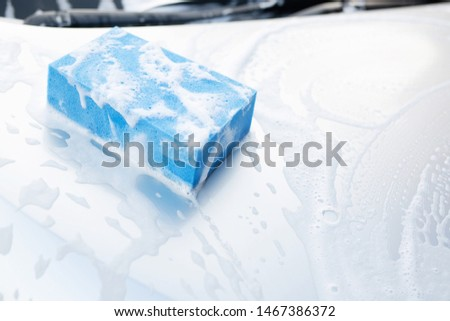 blue sponge and soap over the car for washing. Motor hood being cleaned. Concept car wash clean. Leave space for writing messages.