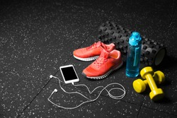 Blue sportive bottle, bright pink training shoes, yellow dumbbells, black pilates mat and smartphone on a black floor background. A colorful set of sportive accessories for gym training. Copy space.