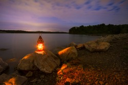 Blue Springs Lake located outside of Kansas City, Missouri at night with a lantern glowing light onto the rocky shoreline