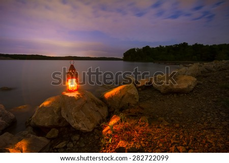 Shutterstock Blue Springs Lake located outside of Kansas City, Missouri at night with a lantern glowing light onto the rocky shoreline