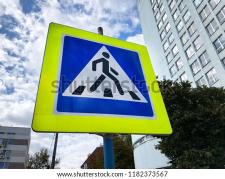 blue square road sign pedestrian crossing. Pedestrian crossing sign on the yellow shield with city background