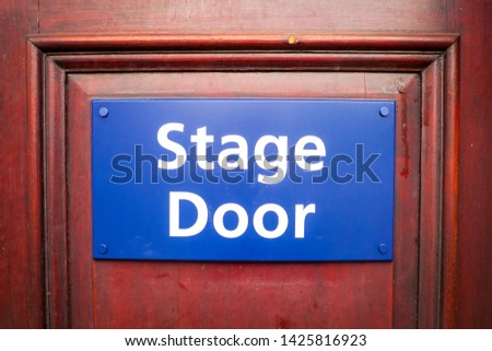 Blue Stage Door sign on a dark wooden door. #1425816923