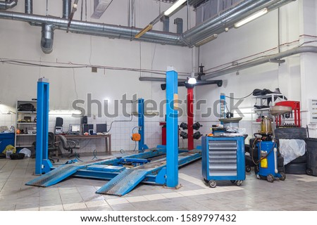 Blue stand wheel alignment convergence of the car during regular maintenance in the workshop for repair of vehicles . Auto service industry.