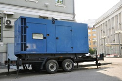 Blue standby mobile diesel generator for office building connected by cable wire to office building