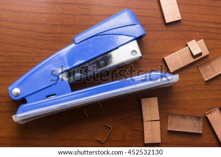 Blue stapler and piles of copper office staples on wooden office, closeup, top view