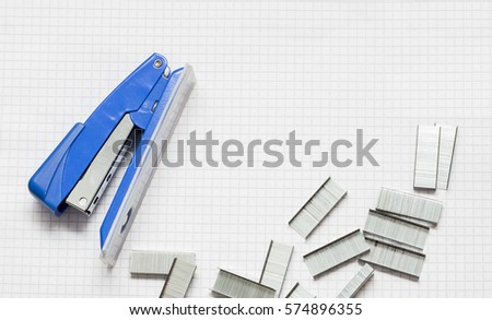 Blue Stapler and Piles of office Staples on Piece of Paper, Closeup