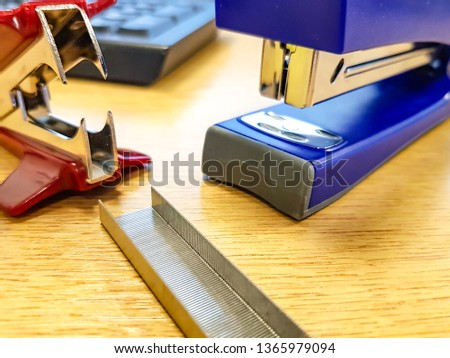 blue stapler, red staple remover, staples pack on wooden table
