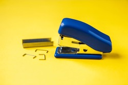 Blue stapler with metal staples on yellow background. Copy, empty space for text