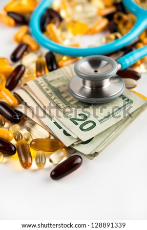 Blue Stethoscope on Pile of Yellow Colored Supplements and American Twenty Dollar Bills