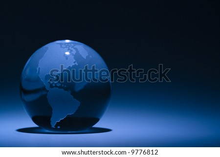 Blue still life of globe showing South America and North America.