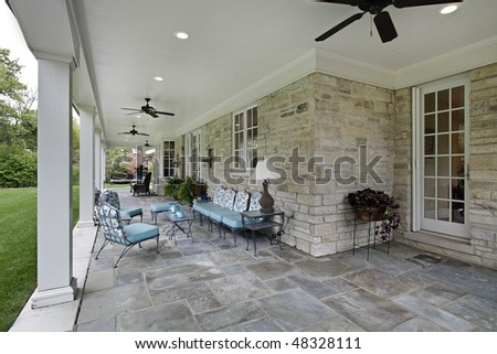 Blue stone patio with columns and blue furniture