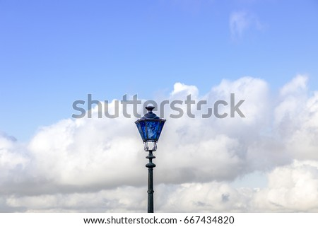 Blue street lamp french old style on blue sky and white clouds background