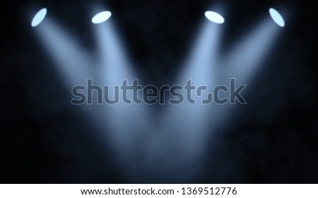 Blue studio spotlight . Stage with smoke on the floor background. #1369512776
