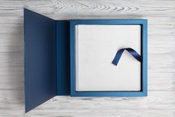 blue stylish square cardboard box for a photoalbum. Bright original box for white wedding album. leather family photo book in the open box blue cardboard box for a photobook