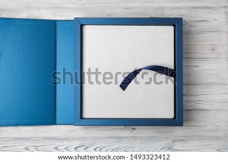 blue stylish square cardboard box for  photo album close up. Bright original box for white wedding album with space for text. leather family photo book in the open box blue cardboard box for photobook Сток-фото ©