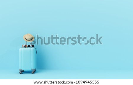 Photo of  Blue suitcase with sun glasses, hat and camera on pastel blue background. travel concept. minimal style