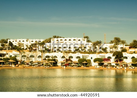 Blue Summer beach with city under morning sun in Egypt Sharm el-sheikh