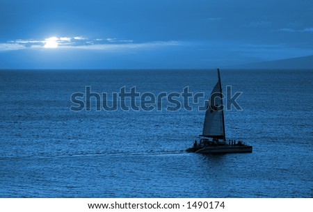 Blue Sunset - a large catamaran sails calmly through seas in Maui, Hawaii. Gorgeous at full size. - stock photo