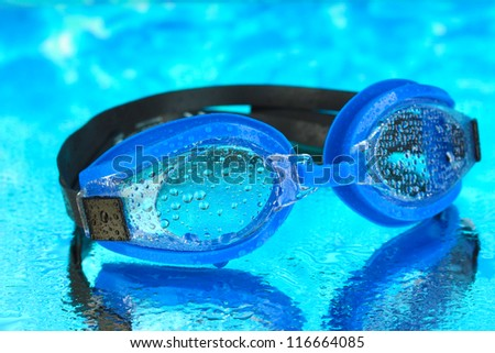 blue swim goggles with drops on blue sea background