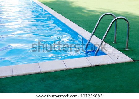 blue swimming pool with stair at hotel close up