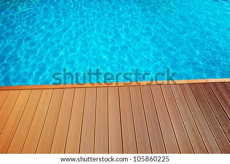 blue swimming pool with wood flooring stripes summer vacation