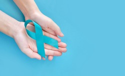 Blue symbolic ribbon - the problem of prostate cancer. Two crossed hands on a blue background