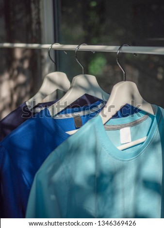 Blue t-shirts on hangers, close up view  #1346369426
