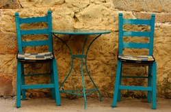 Blue table and chairs against a yellow wall, in Greece
