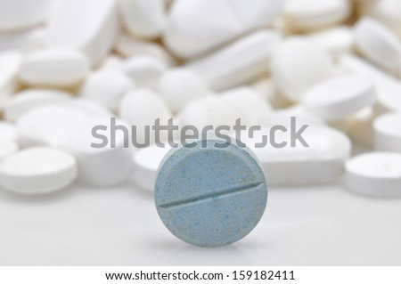 blue tablet among white pills background