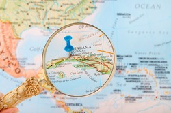 Blue tack on map of Caribbean with magnifying glass looking in on Havana or Habana, Cuba