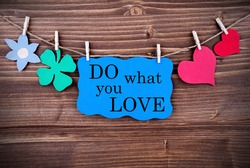 Blue Tag With Phrase Do What You Love On It Hanging on a Line with Different Symbols Like A Flower, Four-leaf Clover And A Heart On Wooden Background