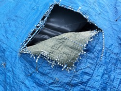 Blue tarp tarpaulin being used to cover a rubbish skip with a torn patch