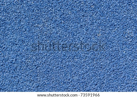 Blue tartan athletic running track texture on the stadium. Tartan track material is the trademarked all-weather synthetic track surfacing for athletics made of polyurethane