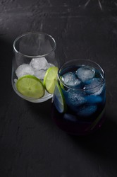 Blue tea with pieces of ice and lime in glass glass on a dark background, vertical background, selective focus