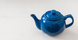 blue teapot on white wooden background