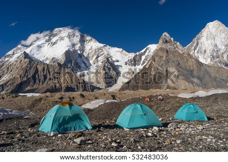 Blue tents at Concordia camp in front of Broadpeak mountain, K2 trek, Pakistan, travel Asia