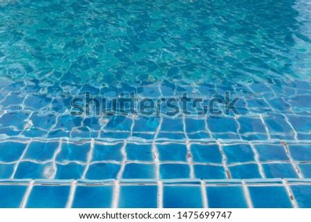 Blue tile steps for walking down to the swimming pool with water waves and reflections from the sun. #1475699747