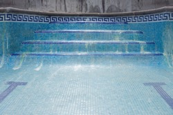 Blue tile swimming pool stairs ladder without water with rests of hydrochloric acid.