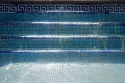 Blue tile swimming pool stairs without water with rests of hydrochloric acid.
