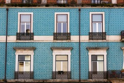 Blue tiles front facade of Lisbon building with windows and small balconies on sunny day. Traditional architecture in Portugal capital, real estate, residential area concepts