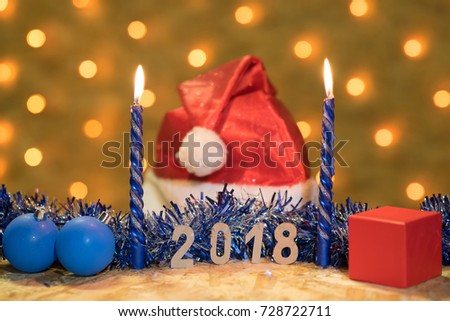 Blue tinsel, a ball, burning candles, a red cap and a gift with figures of 2018 on a wooden table on the background of a New Year's garland with blurred golden lights - Shutterstock ID 728722711